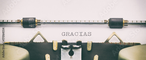 Fotomural  Gracias word in capital letters on white sheet