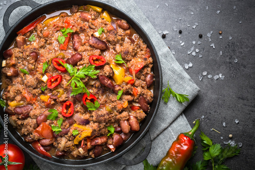 Chili con carne in iron pan on black background Canvas Print