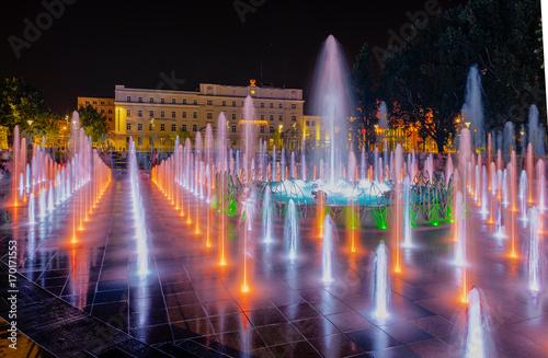 Obraz Night colorful fountain show inLublin park. Vivid color fountain water - fototapety do salonu