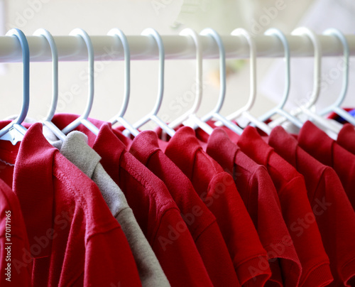 Fotografía  Red and one gray school uniform shirts on hangers