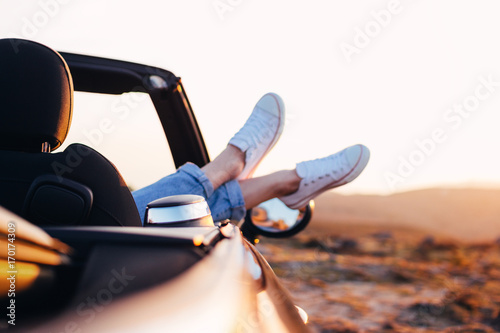 Trendy hipster woman rests and admire sunset in mountains from her cabriolet car. Happy female relaxing pushes her shoes out of convertible enjoy view - 170174309