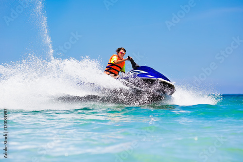 Photo Stands Water Motor sports Teenager on water scooter. Teen age boy water skiing.