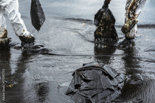 Photo Workers remove and clean up crude oil spilled with absorbent paper