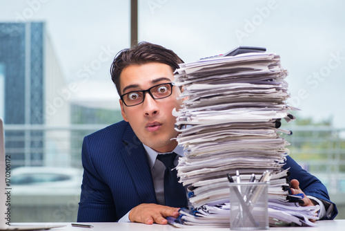Fotografie, Obraz Businessman with pile stack of paper paperwork in the office