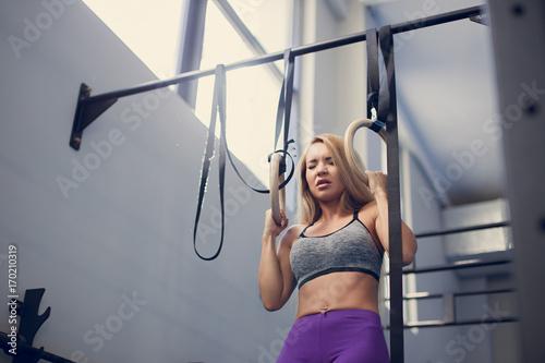 Zdjęcie XXL piękny fitness kobieta trening fitness gimnastyczne pierścienie słoneczny zewnątrz. Sporty dziewczyna robi siedzieć podnosi na gimnastycznych pierścionkach