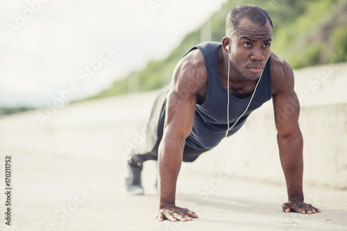 Fototapeta Portrait of a young black man doing push ups at the beach