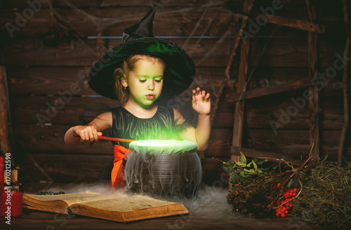 Fototapeta Halloween. little witch child cooking potion in   cauldron with spell book obraz
