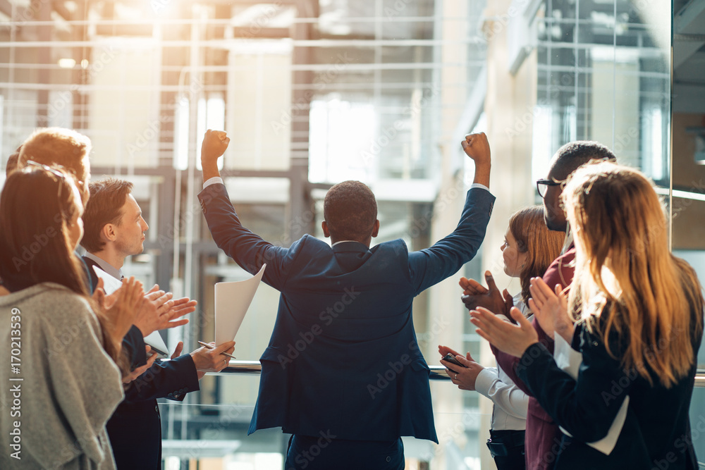 Fototapeta Group of ecstatic business partners looking at camera with raised arms