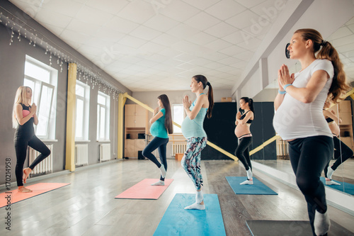 Photo Happy pregnant women in yoga class standing in tree pose in a fitness studio