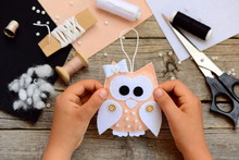 Small Girl Shows A Felt Christmas Tree Decor. Small Girl Holds A Christmas Tree Decor Owl In His Hands. Homemade Decoration Idea For Kids. Craft Tools And Materials On A Wooden Table. Closeup