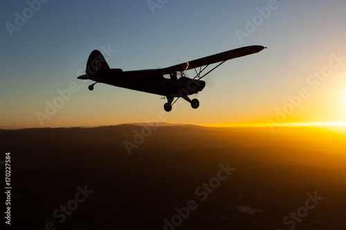Romantic airborne evening: beautiful silhouette of a plane flying towards the se Wallpaper Mural