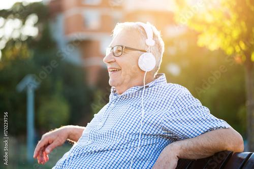Zdjęcie XXL Plenerowy portret starszy mężczyzna który jest słuchającym muzyką na hełmofonach.