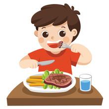A Cute Boy Is Eating Steak Wit...