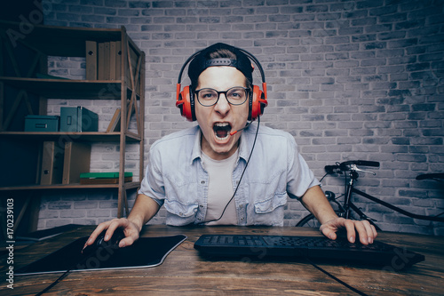 Foto  Young man playing game at home and streaming playthrough or walk