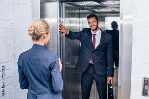 Photo  businessman holding elevator door for woman
