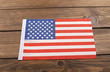 Studio shot of small bright flag of USA lying on wooden background. Copy space.
