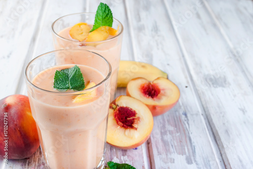 Poster de jardin Lait, Milk-shake Berry smoothies of apricot, peach and banana in glasses and ingredients on a wooden table