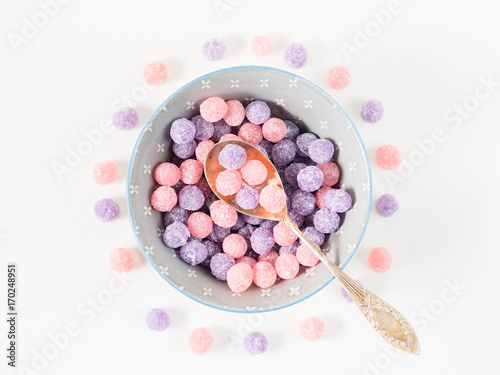 Foto op Aluminium Snoepjes Round purple and pink bonbon candies sweets in gray bowl on white canvas background. Minimal still life