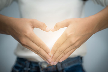 woman hand making  heart shape with her fingers in front of her chest