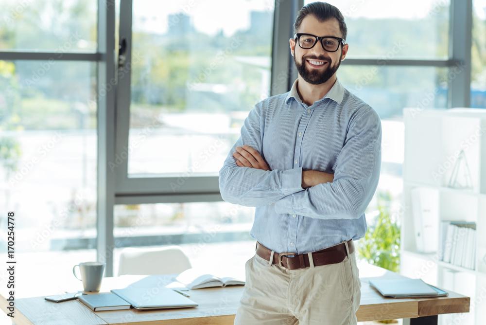 Fototapeta Cheerful bearded man posing in his new office