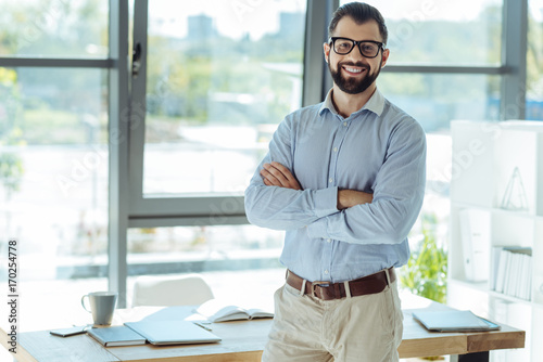 Fototapeta Cheerful bearded man posing in his new office obraz