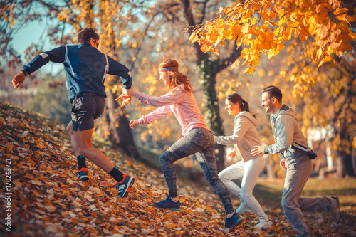 Foto op Canvas Jogging Group of young friends jogging at the park.Autumn season.They run up the hill and making fun.