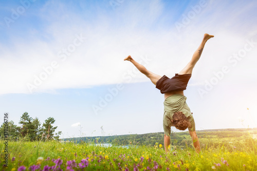 Fotografia  Young man doing a handstand on a filed.