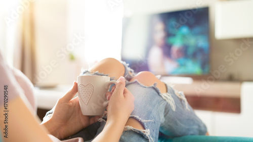 Photo Beautiful young woman relaxing on the sofa at home, watching tv and enjoying cof