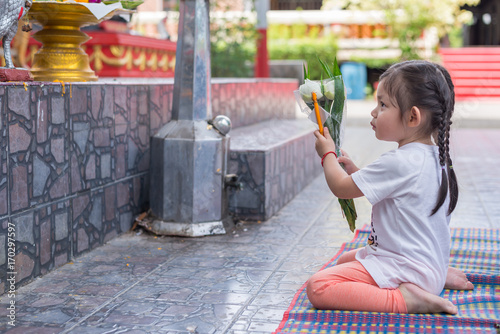 Sweet little Asian girl sitting and praying with lotus
