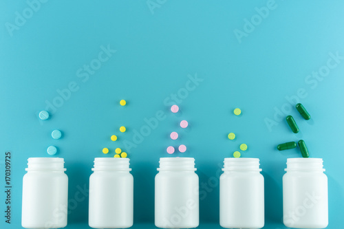 Fotografia  Medicines, supplements and drugs in a bottle on blue background