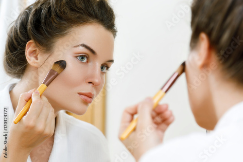 Photo Woman applying foundation or blusher on her face