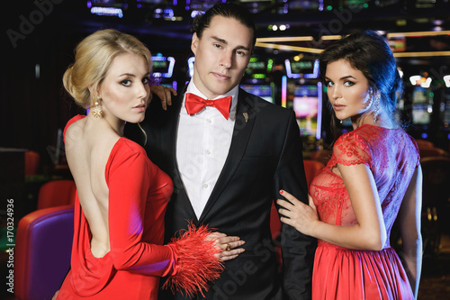 Cuadros en Lienzo  Confident man and two beautiful women in the casino