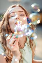 Happy Woman Blowing Soap Bubbl...