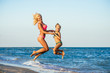 Action portrait of young mother with daughter jumping together on beach. Laughing girls in swimwear