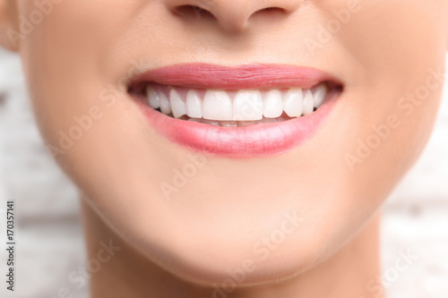 Fotografie, Obraz  Young beautiful woman with healthy teeth smiling on light background, close up