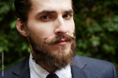Photo  Young employee with beard and moustache looking at camera