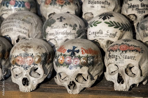Pinturas sobre lienzo  Skulls painted with names, colorful flowers and crosses in the Charnel House or