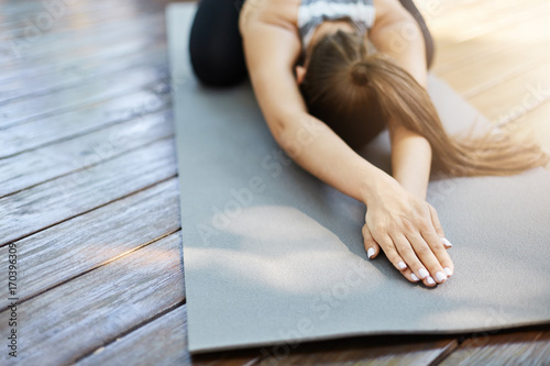 Staande foto School de yoga Close up of hands doing yoga or pilates laying on a grey mat in a temple or a backyard.