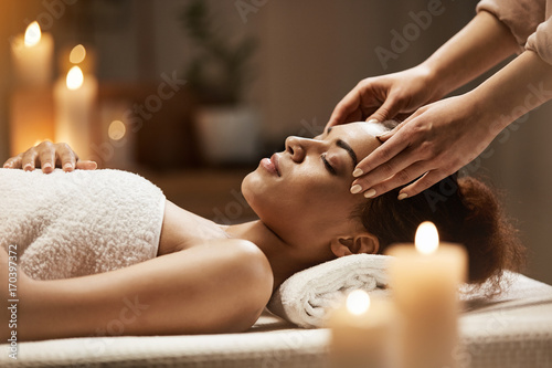 Attractive african girl enjoying face massage in spa salon.