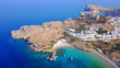Aerial drone photo of famous beach of Lindos with turquoise waters and iconic ancient Acropolis - village of Lindos, Rodos island, Aegean, Dodecanese, Greece