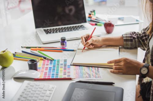 Zdjęcie XXL Młody azjatykci żeński projektant używa grafiki pastylkę podczas gdy pracujący z komputerem przy studiiem lub biurem.