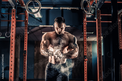 Valokuva Strong muscular man preparing for workout in crossfit gym