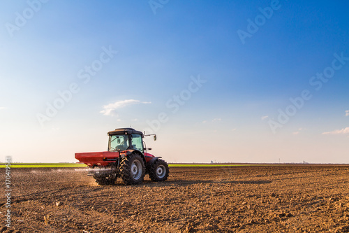 Valokuvatapetti Farmer fertilizing arable land with nitrogen, phosphorus, potassium fertilizer