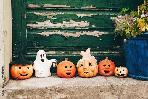 Outdoor halloween decorations against old green door