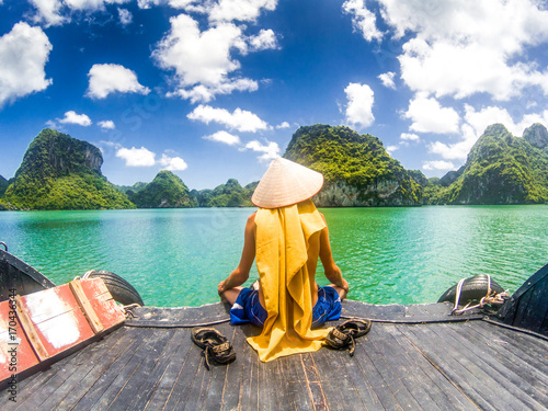 Leinwand Poster man wearing a Vietnamese hat enjoying the magnifiecent sight of Ha Long bay lime