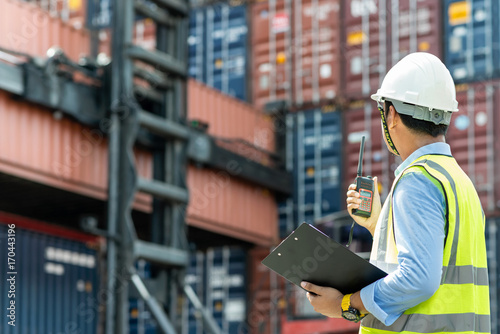 Fotografía  Foreman control loading Containers box from Cargo freight ship for import export