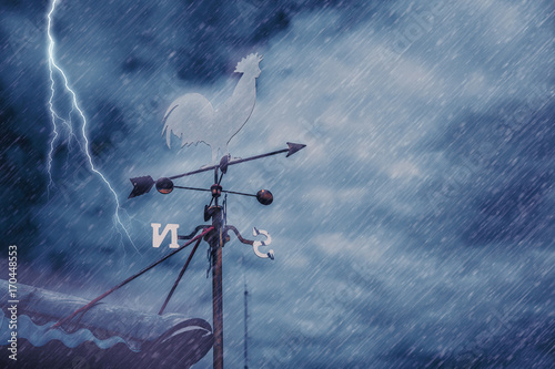 Leinwand Poster wind vane on house roof with background of storm raining windy black cloudy dark