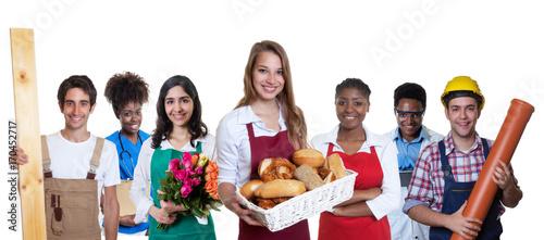 Fotografía  Sympathische Bäckereiverkäuferin zweigt Daumen mit anderen Azubis