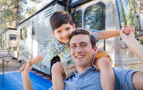 Happy Young Caucasian Father and Son In Front of Their Beautiful RV At The Campground.