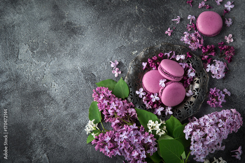 Poster Macarons beautiful lilac flowers and blackberry macarons on vintage plate over grey texture background